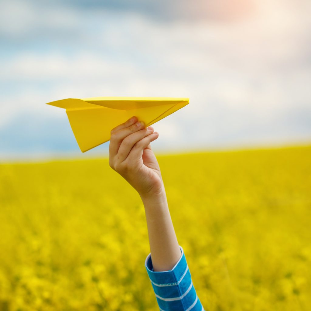 Paper airplane in children hands on yellow background and blue s